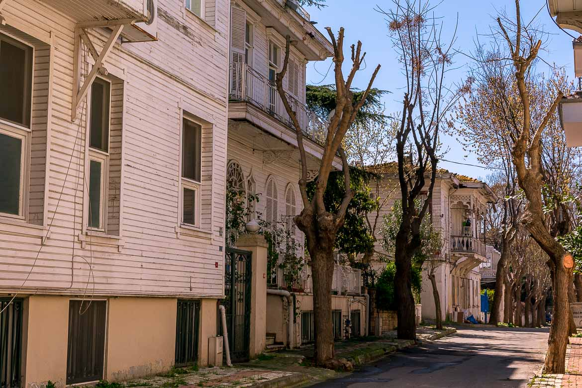 This photo shows a quiet street on Buyukada island lined with magnificent white wooden mansions.