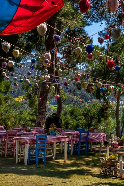 This is an image of the outside seating area at the Lovers Hill Café on Buyukada Island. There are tables covered with red checkered tablecloths on the lawn and coloured chairs. There are colourful tents and decorations hanging over the tables.