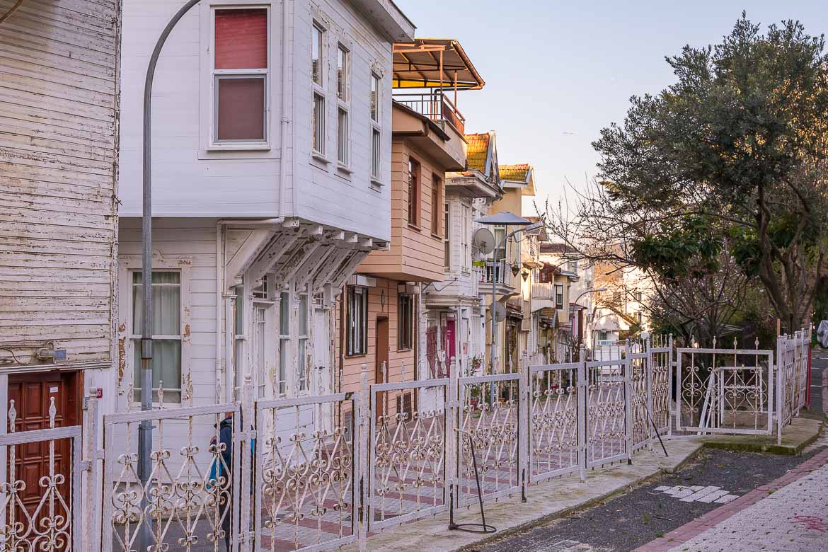 This photo shows a street on Heybeliada Island lined with pastel coloured wooden mansions.