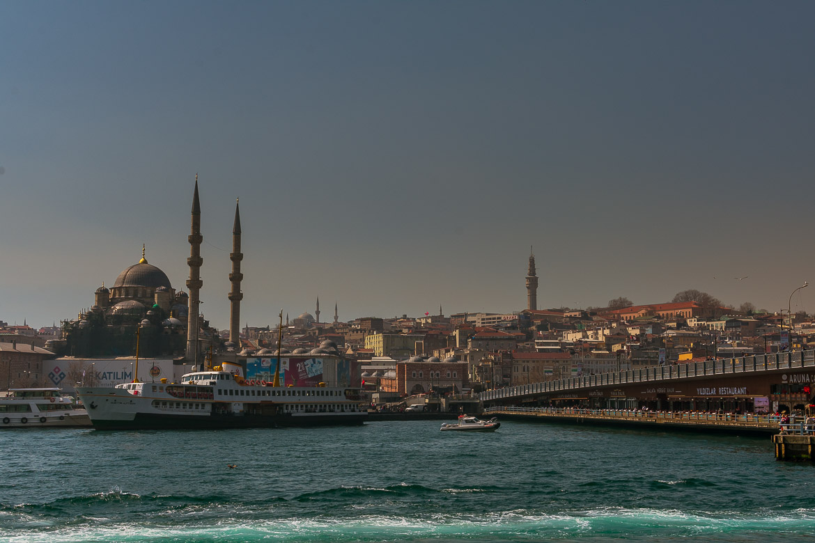 This image shows a Sehir Hatlari ferry in front of Galata Bridge in Istanbul Turkey.