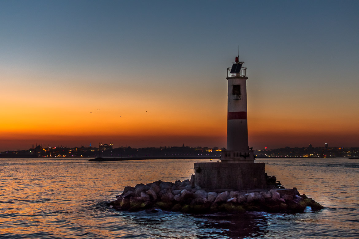 This image shows a lighthouse in the Sea of Marmara. In the background the silhouette of the city of Istanbul during sunset.