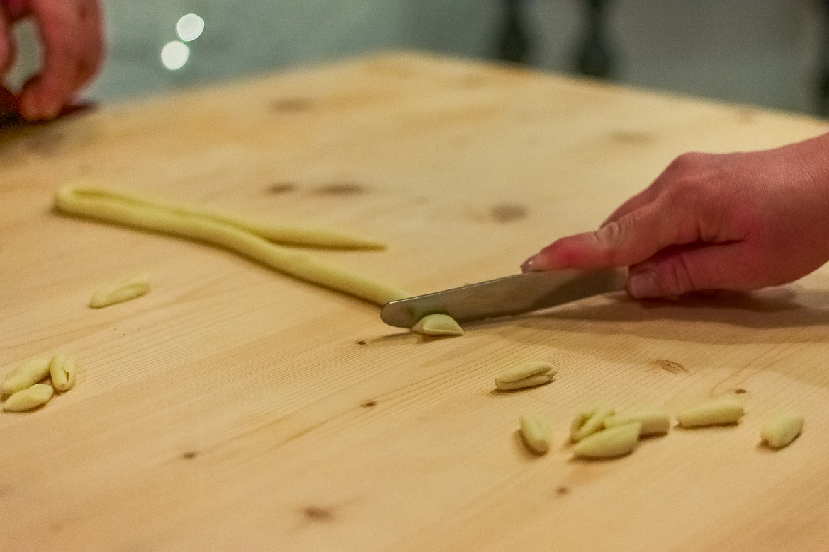 This image is a close up of Maria's hand as she uses a knife to cut fresh pasta dough.