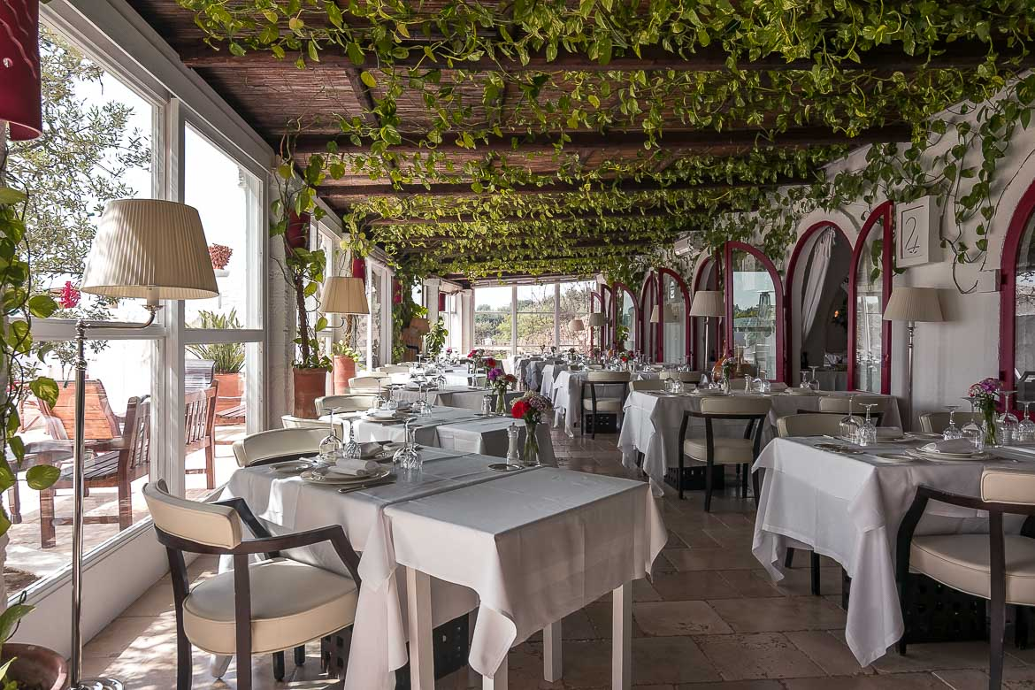 This image shows the interior of the restaurant at Masseria Torre Coccaro. There are tables with white tablecloths and the room is brught and sunny.
