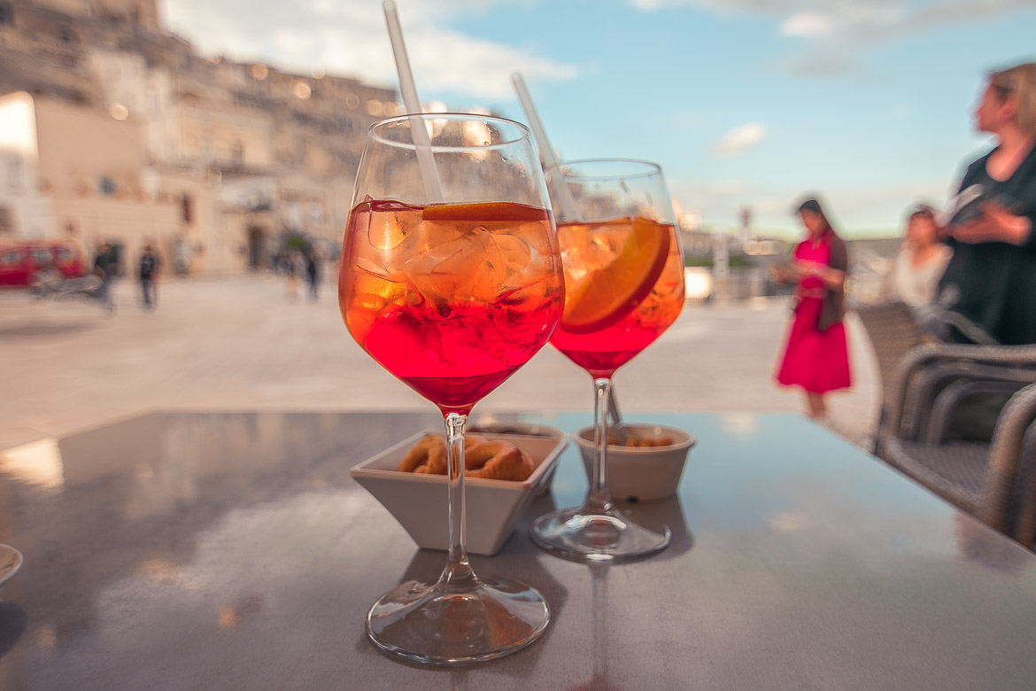 This is a close up of two Aperol Spritz cocktails with a bowl of tarallini on the side.