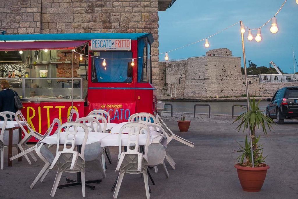 This photo shows a food truck on Trani promenade selling fried fish. The food truck is red and there is a line of lights hanging above. There are white tables and chairs. This photo is indicative of the simplicity of food in Puglia and this is why we chose it as the featured image for our Puglia food guide.