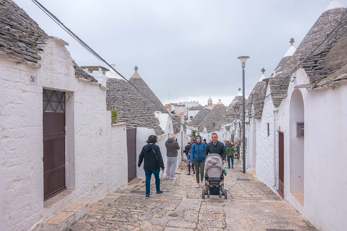 This image shows a picturesque street in Rione Monti, Alberobello. The street is lined with gorgeous trulli on both sides. There are many people walking along the quaint street.