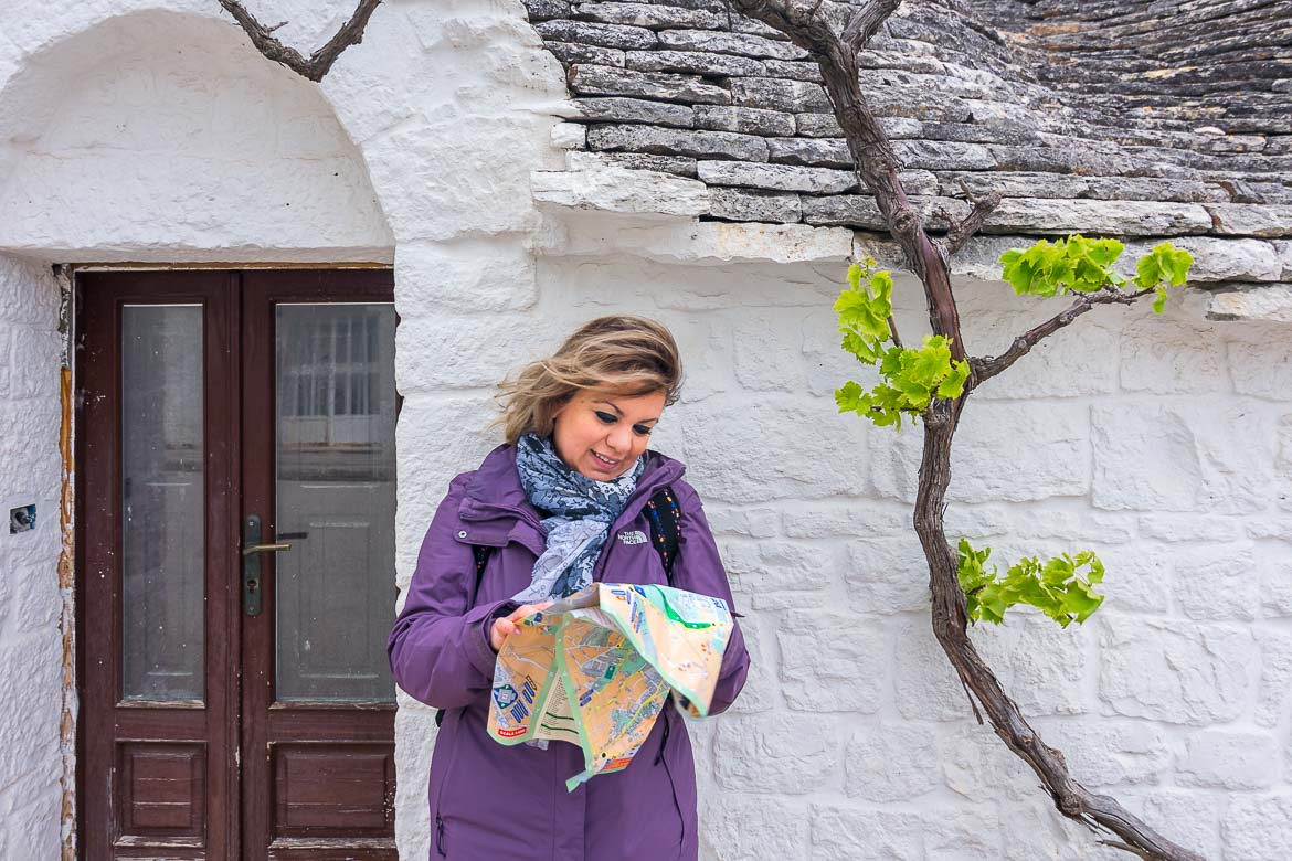 This image shows Maria holding a map in front of a traditional trullo in Alberobello.
