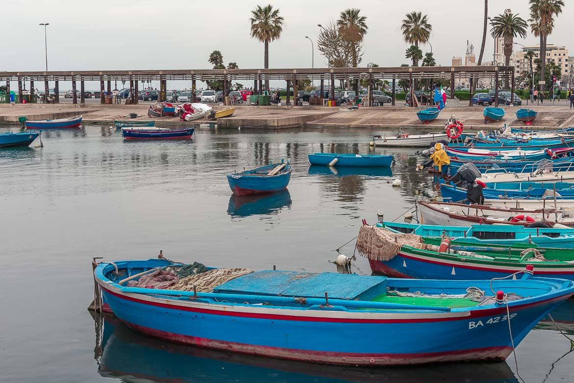 This image shows the old port in Bari with the iconic blue fishing boats.
