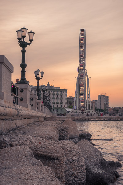 This photo was shot along the promenade of Bari at sunset. The Bari Ferris Wheel is in the background. The sky is a gorgeous peach colour.