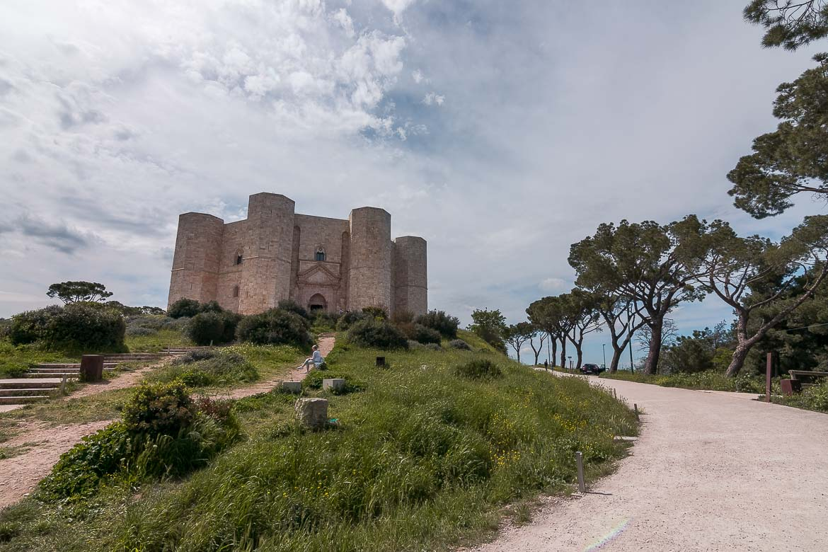This image shows the impressive Castel del Monte. It's built atop a hill and surrounded by gorgeous countryside.