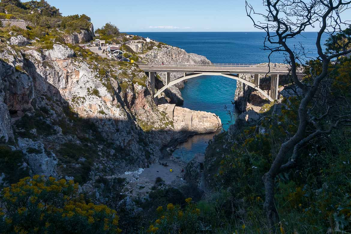 This is a panoramic shot of Ciolo Bridge. The bridge stands impressively above a natural fjord in the midst of dramatic cliffs.