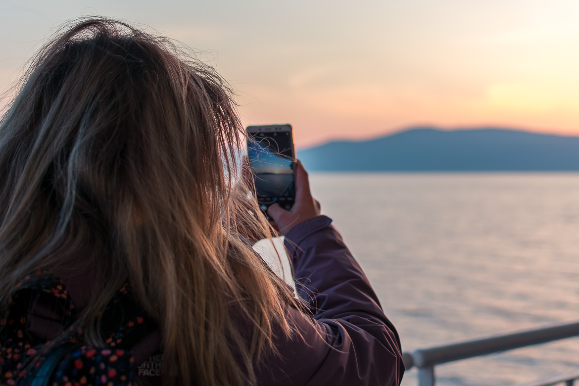 This image shows Maria with her back turned on the lens as she snaps a shot of the sunset with her cell phone. The sky is red and yellow and the sea is absolutely calm.