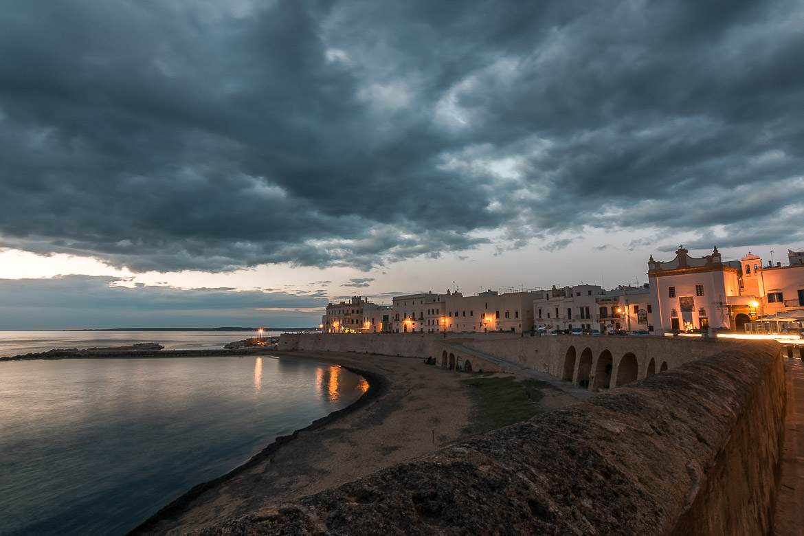 This is an image of beautiful Gallipoli at sunset. The sky is dramatic and the street lights reflect on the calm sea. Gallipoli is an essential stop on any Puglia road trip.