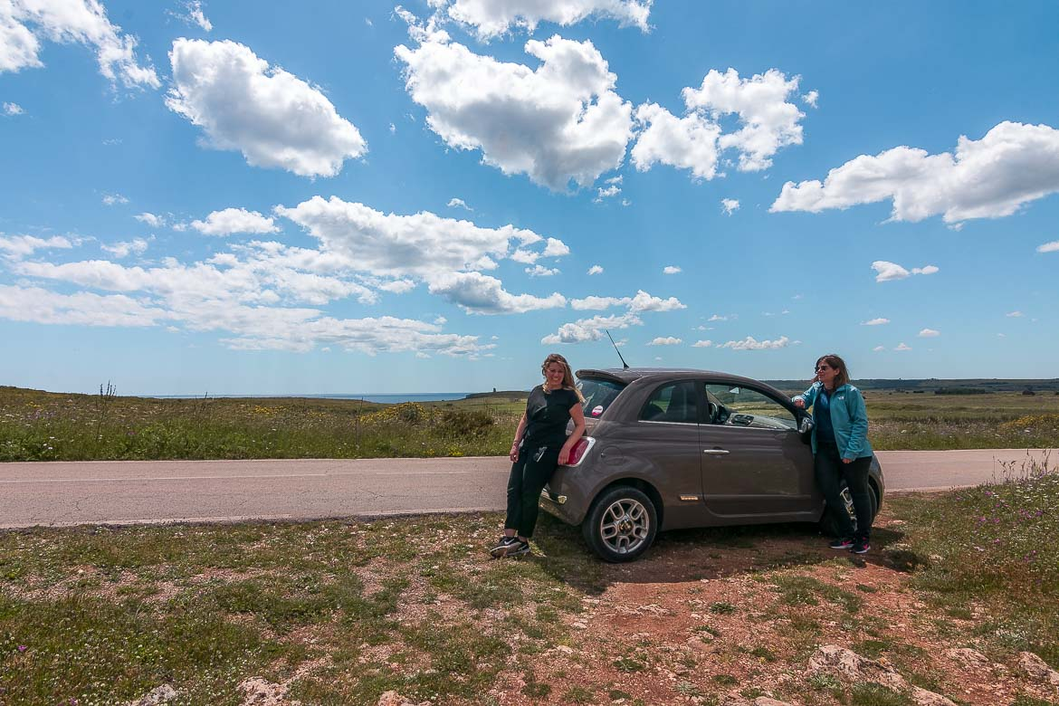 This image shows Katerina and Maria posing in front of their FIAT 500 at the side of the road in the midst of gorgeous countryside.