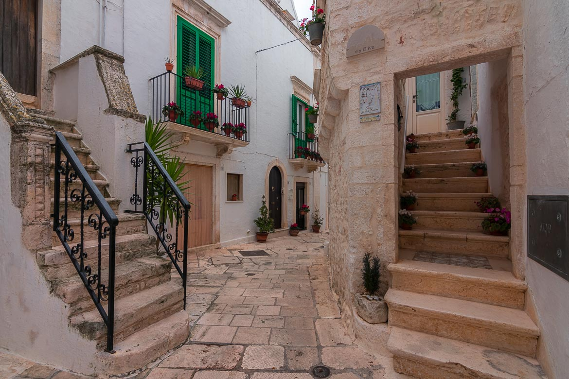 This is a courtyard of sorts in Locorotondo Old Town. There are traditional buildings with green shutters and pots with flowers.