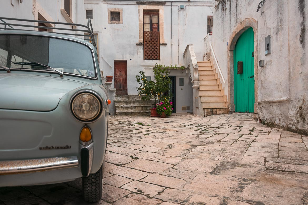 This photo shows a light blue vintage car parked in the historic centre of Martina Franca.