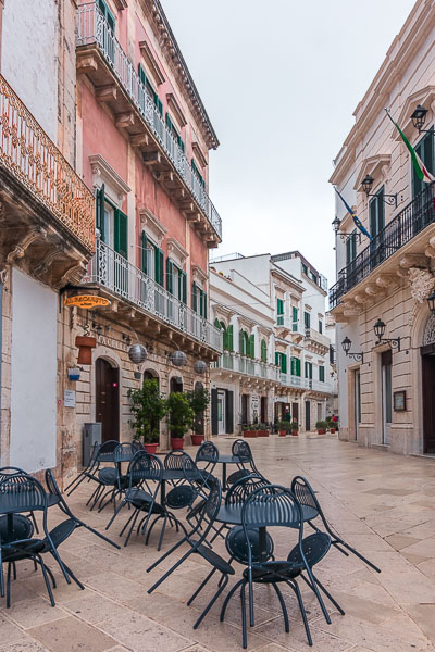 This image shows Martina Franca during siesta time. The town is completely empty. In the foreground, the tables and chairs of a cafe.