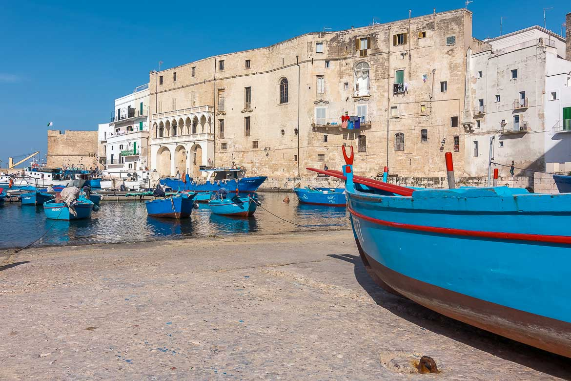 This image shows the quaint Old Port in Monopoli with the iconic blue fishing boats and the gorgeous Italian architecture.