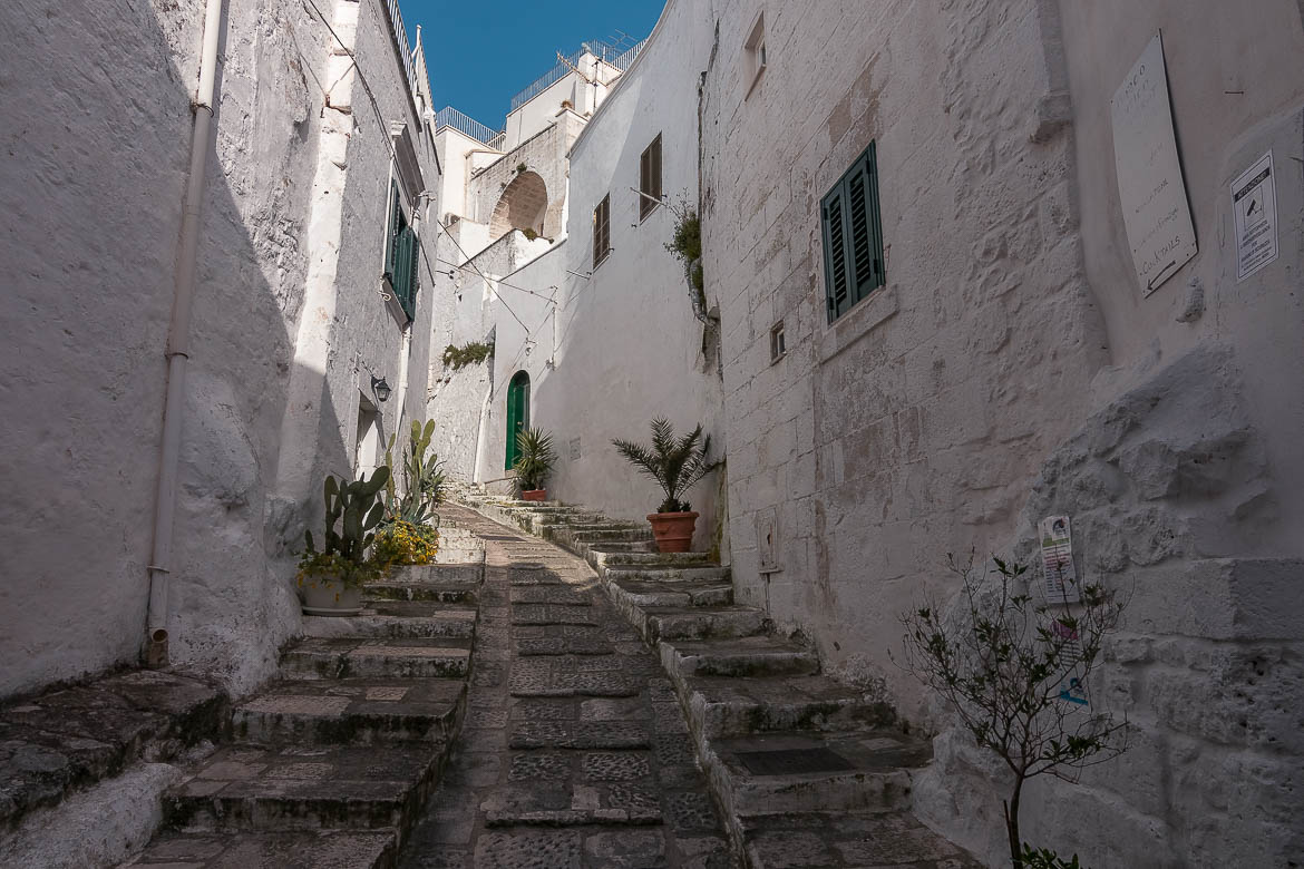 This image shows an uphill path with steps in Ostuni Old town. It is lined with traditional whitewashed buildings with colourful shutters. Ostuni is almost identical to a Greek Island Chora.