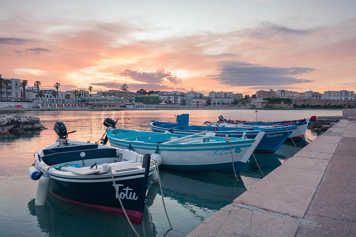 This is an image of the small port of Otranto at sunset. In the foreground, a series of traditional fishing boats. In the background, the sky looks as though it's on fire.