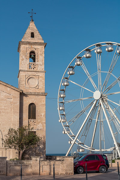 This is a close up of a bell tower standing right beside a Ferris wheel in Savelletri.