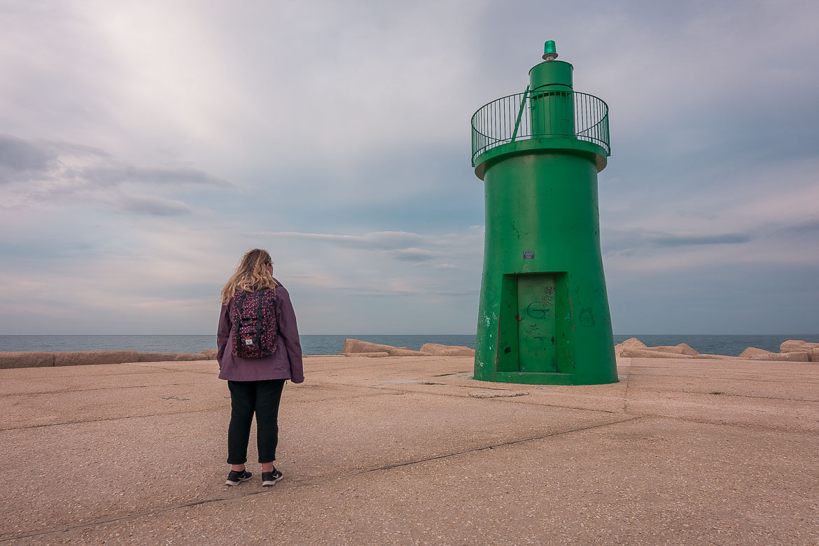 This image shows Maria standing in front of a green lighthouse in Trani.