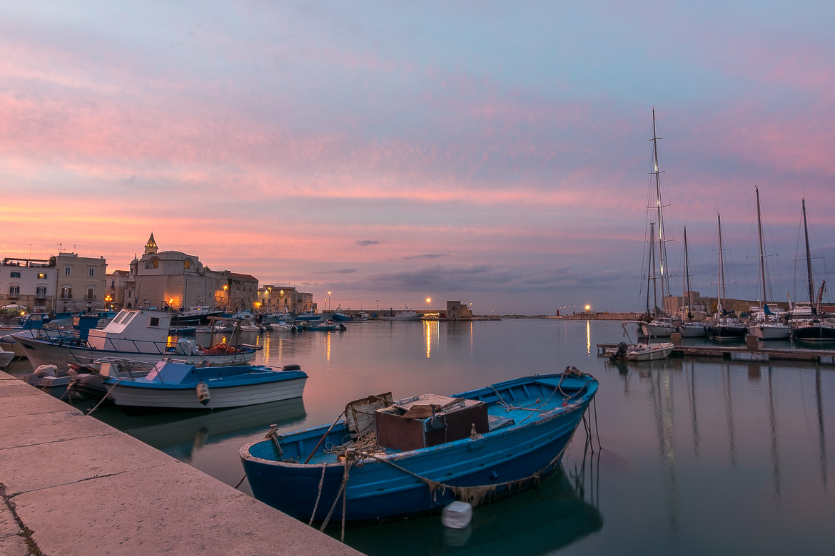 This image shows the promenade of Trani at sunset. The sky is the most impressive pink and the sea is so calm that it's like a mirror.