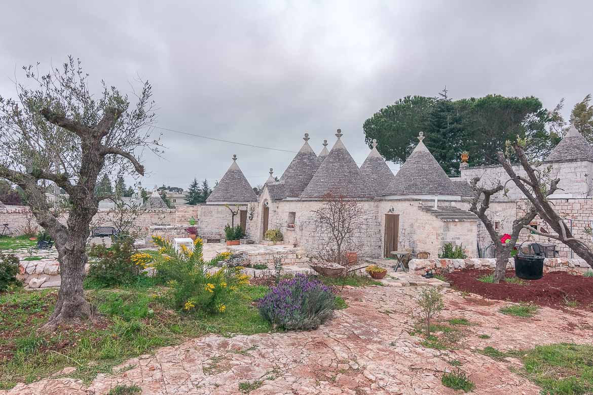 This image shows a complex of trulli, which are white round stone buildings with grey conical roofs. Puglia is abundant in trulli. You shouldn't miss the chance to stay at one during your Puglia road trip. This is Annalocos Trulli in Locorotondo. We spent one night there and loved it.