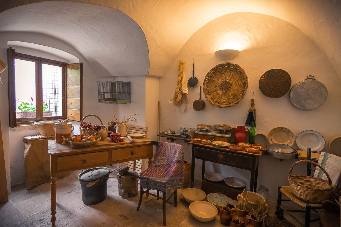 This is a room inside Trullo Sovrano. There are kitchen tools, plates and pots on display, hanging from walls or resting on tables.