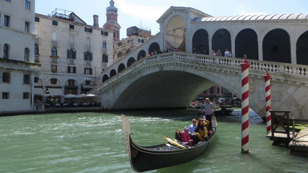 This photo shows the Rialto bridge in Venice, Italy with a gondola having just passed underneath it. What to do in Venice: our complete guide to La Serenissima.