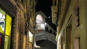 This is a photo of the Rialto bridge in Venice at night with the moon right above it. What to do in Venice: our complete guide to La Serenissima. Venice Italy.
