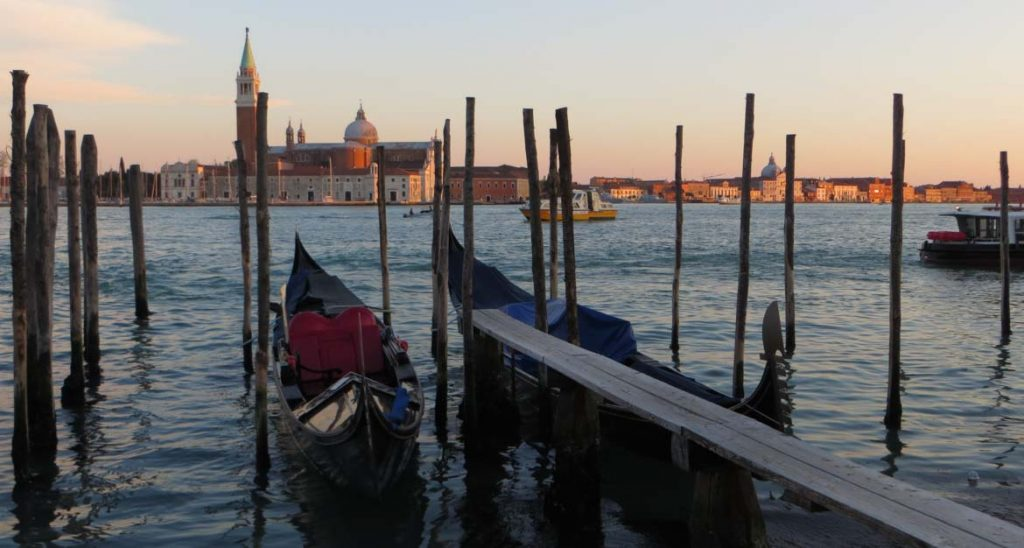 This photo shows the view from Riva degli Schiavoni in Venice, Italy, during sunset. What to do in Venice: our complete guide to La Serenissima.