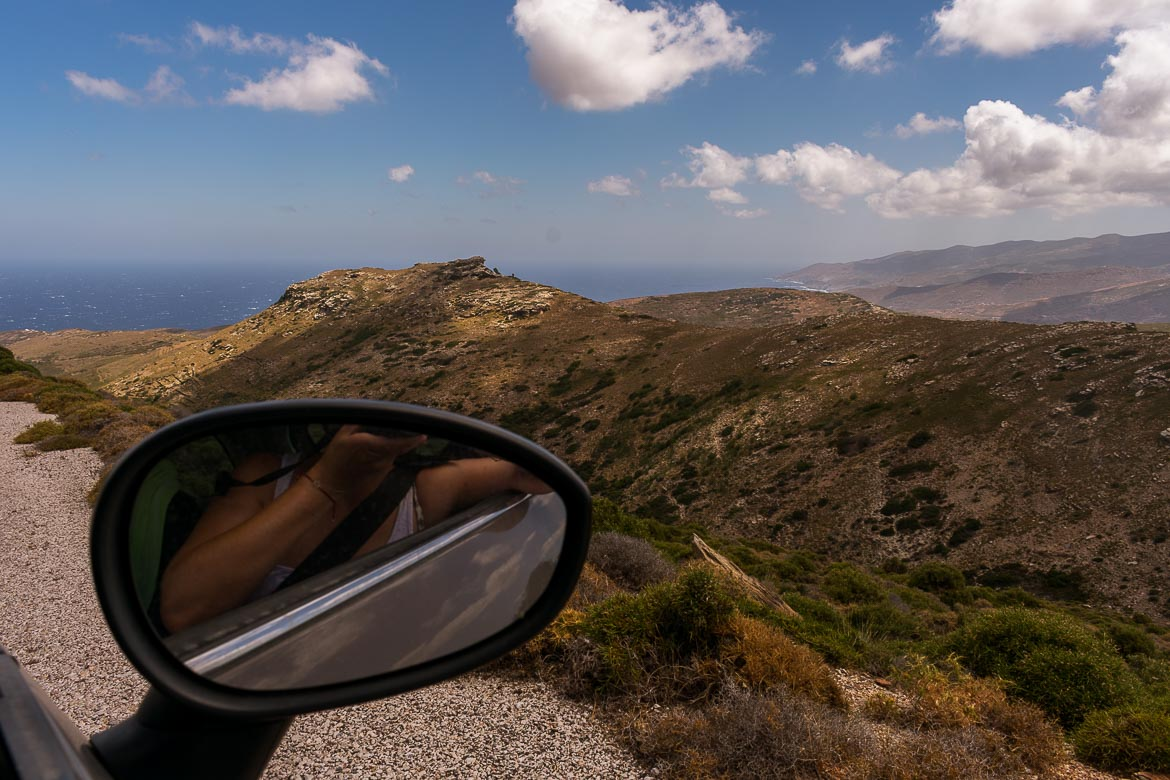 This image shows a bare mountain with the blue sea in the background. In the foreground, Katerina's reflection as she snaps a photo with her camera.