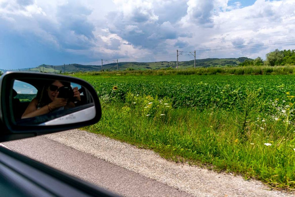 This image shows the green Romanian countryside as we drive along a road. There is the reflection of Katerina shooting the photo on the car mirror. This is the featured image on our Romania road trip article.