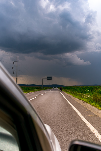 This image was taken from the car while we drove. The road is empty. The only thing in sight are the ominous dark grey clouds in the distance.