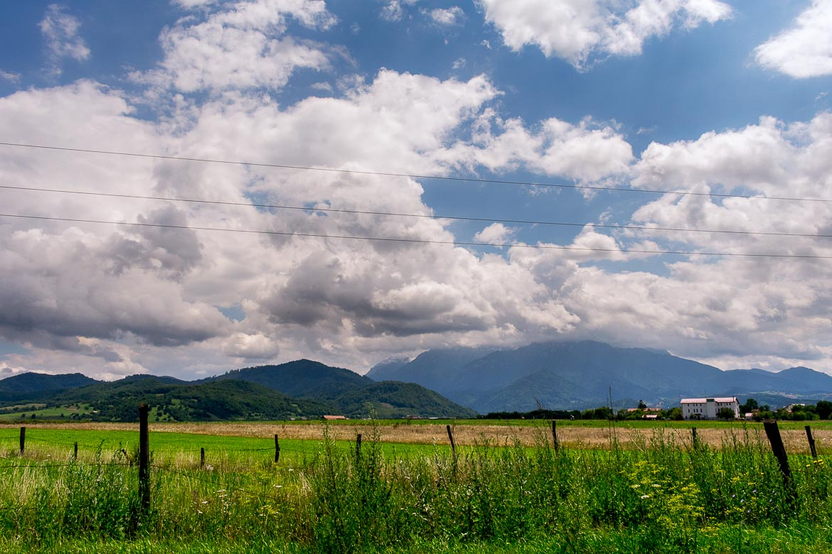 This is an image of the Romanian countryside as we saw it during our week-long Romania road trip. There is lush greenery everywhere and a beautiful sky above.