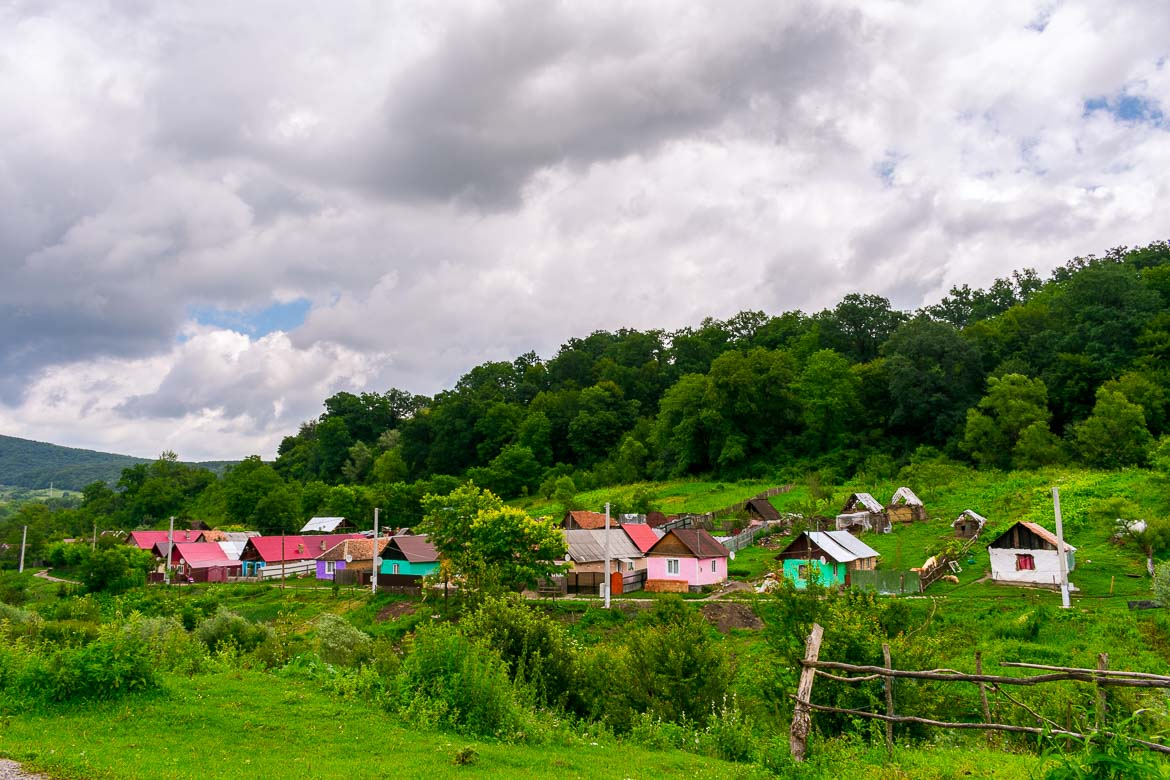This image shows a cluster of vividly coloured houses surrounded by lush greenery in the middle of nowhere in the Romanian countryside.