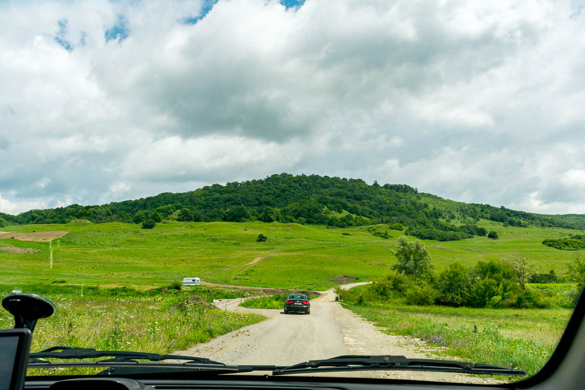 This image shows a dirt road somewhere on our way to Viscri. The scenery is amazing with lush greenery all around.