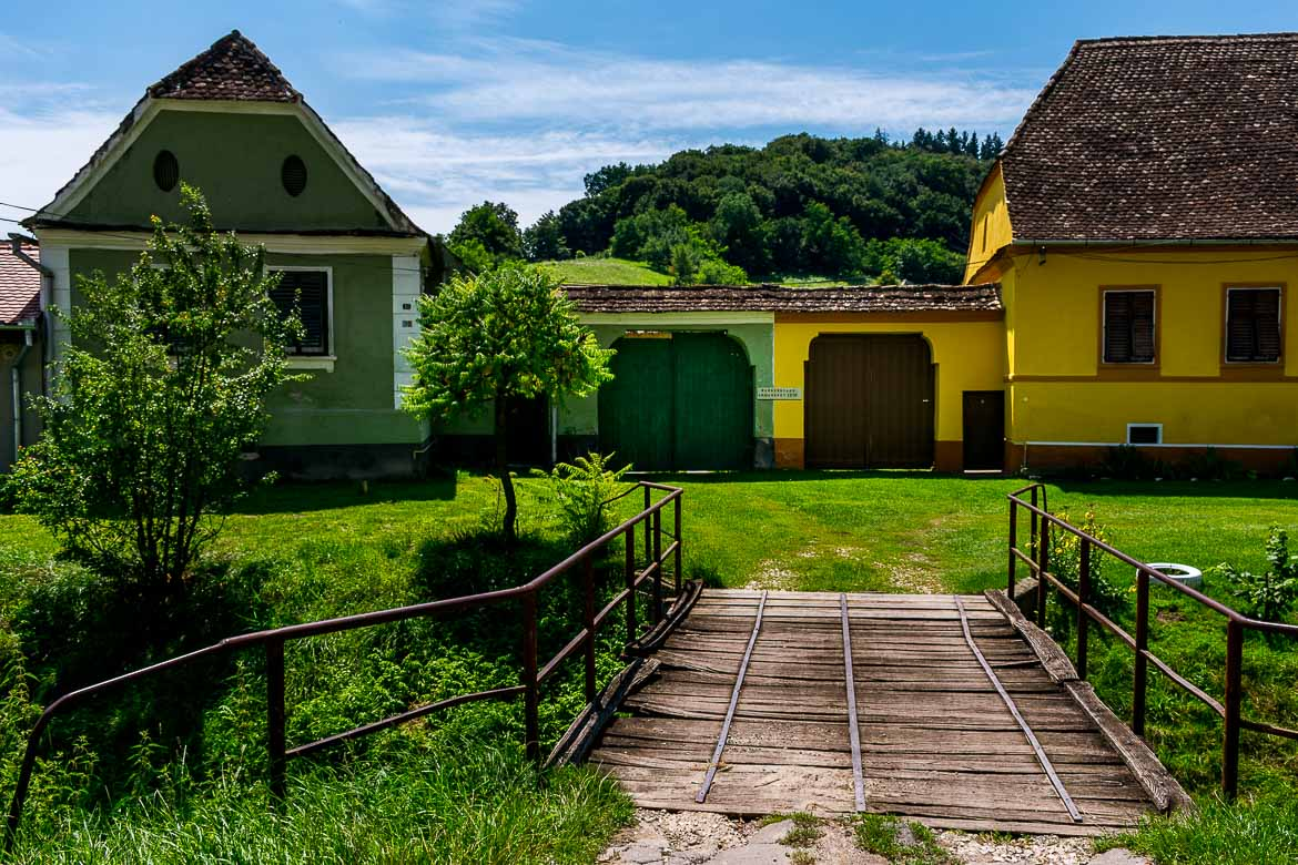 This is an image of Biertan town. There are two brightly coloured houses. One is green the other is yellow. There is grass everywhere and a small wooden bridge in the foreground.