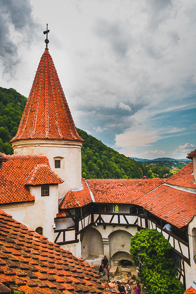 This image shows the interior courtyard and one of the towers at Bran Castle. The castle is white with red tiled roof.