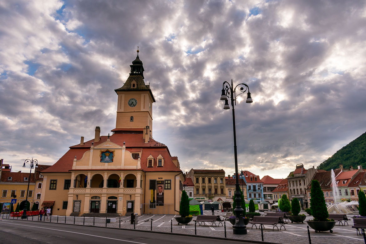 This image shows the Council Square in Brasov Old Town. The former Council House which now houses the Brasov County Museum of History dominates the square. It is a large building with a tower located in the middle of the square. The square is lined with smaller colourful buildings. There are also many benches and a fountain.