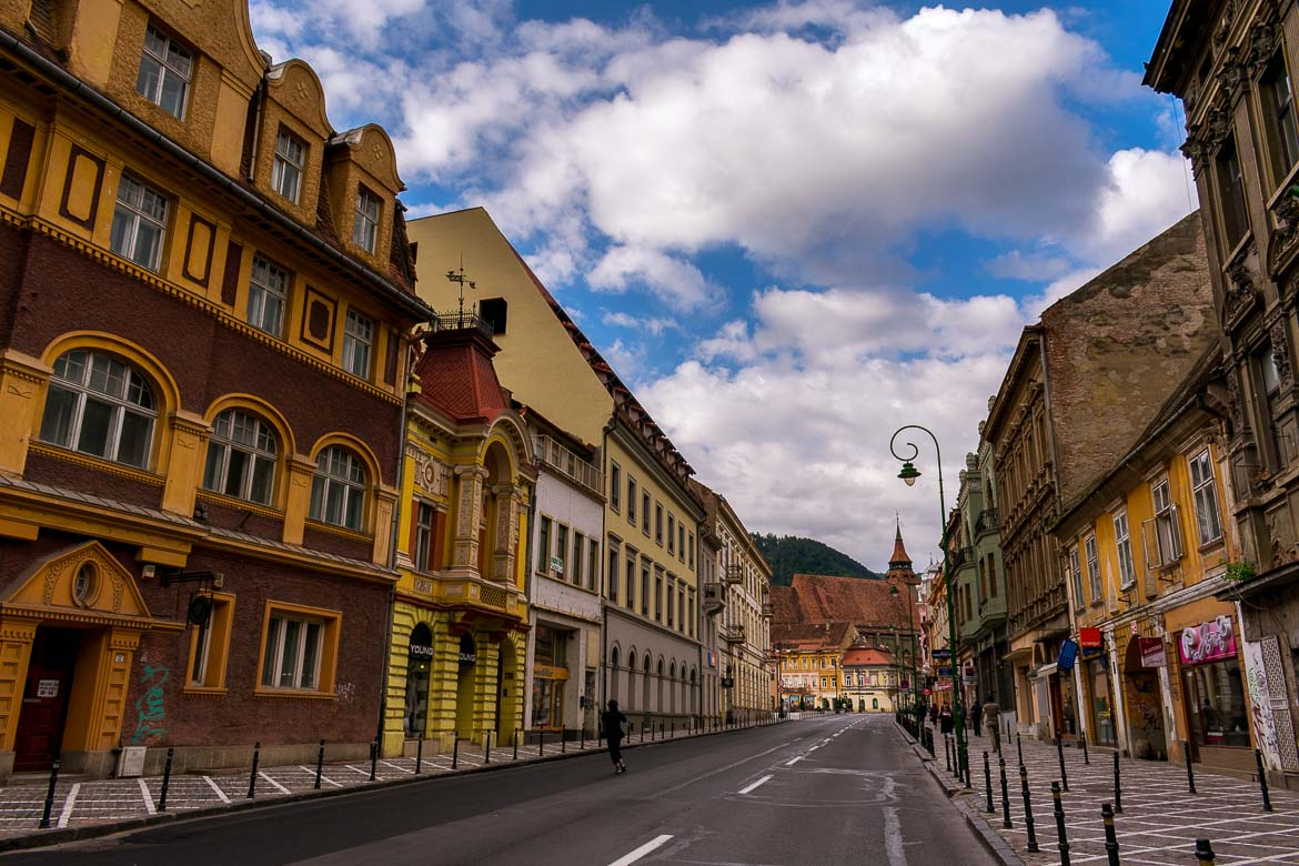 This picture shows the main road that passes through Brasov Old Town completely empty of cars. It's very early in the morning.