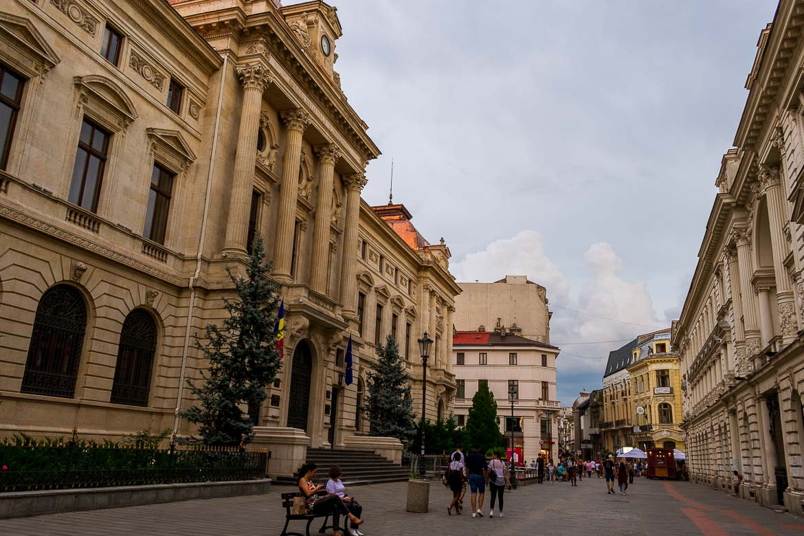 This image was shot on a pedestrianised street in Bucharest Old Town. There are beautiful historical buildings on both sides of the street. It is almost sunset and there are a lot of people walking on the street. Others are seating on benches along the street.