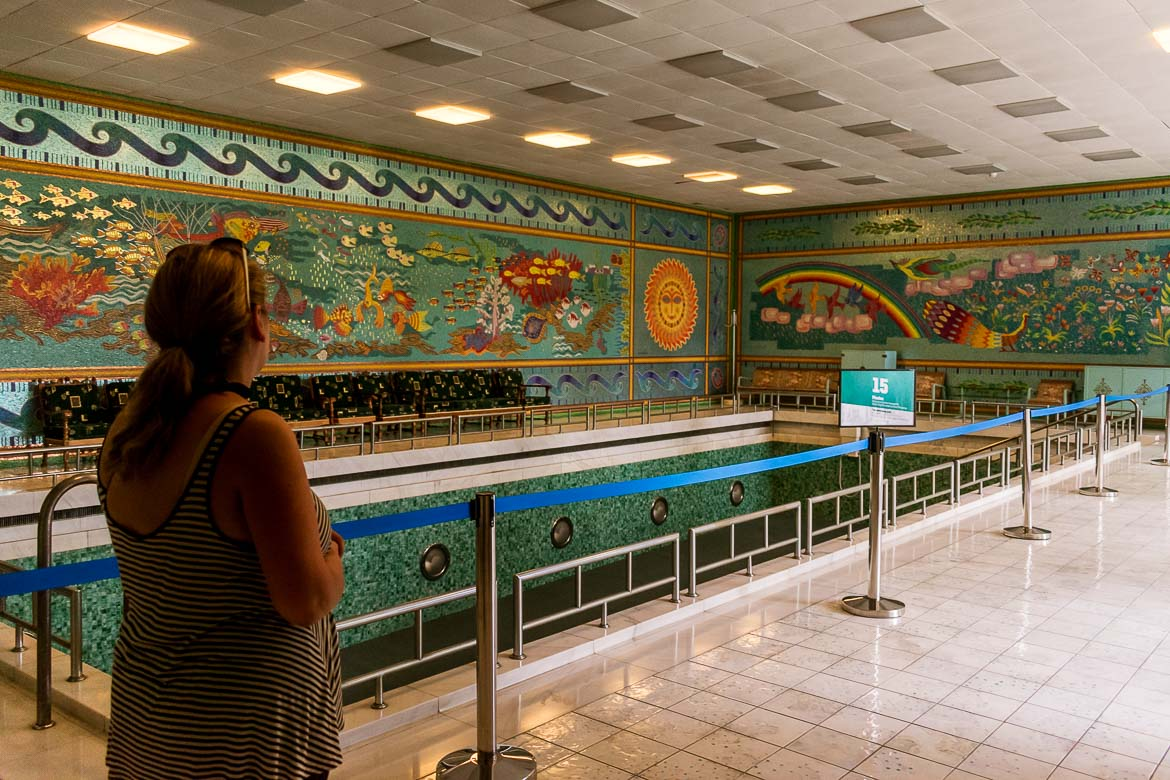 This image was shot inside Casa Ceausescu. More specifically, it shows Maria with her back turned to the camera looking at the massive interior swimming pool. The pool doesn't contain water. Around the pool there are mosaics of vibrant colours on the walls.