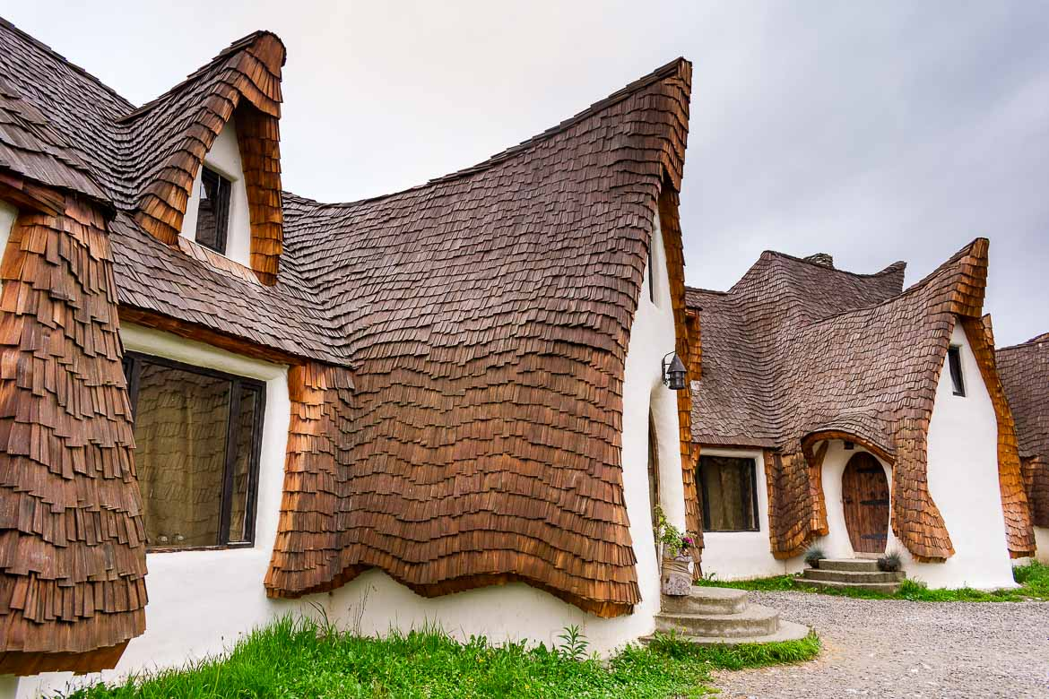 This image shows the buildings at Castelul de Lut Valea Zanelor. Made entirely from natural materials, the buildings look almost surreal. Their shape seems as if it has a flow, a movement. They are white with brown rooftops. They seem as if they have sprung out of a kids' storybook or comic.