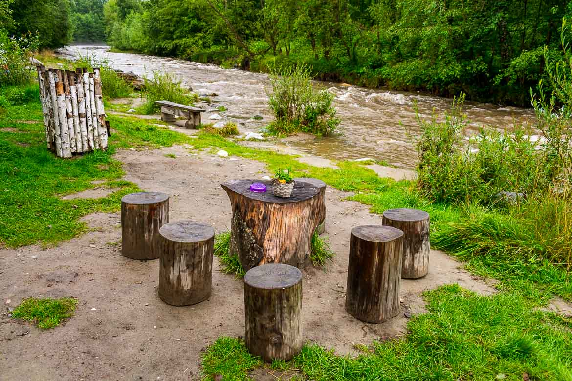 This image shows the area around Castelul de Lut Valea Zanelor. There is a stream flowing along lush greenery. There are tables and stools made of logs and decorated with flowers right next to the stream.