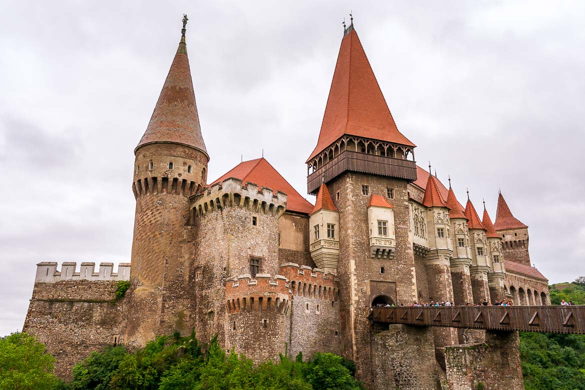 This is an image of Corvin Castle. It is one of Romania's prettiest castles. It has a large drawbridge and many towers and turrets with red tiled roofs.