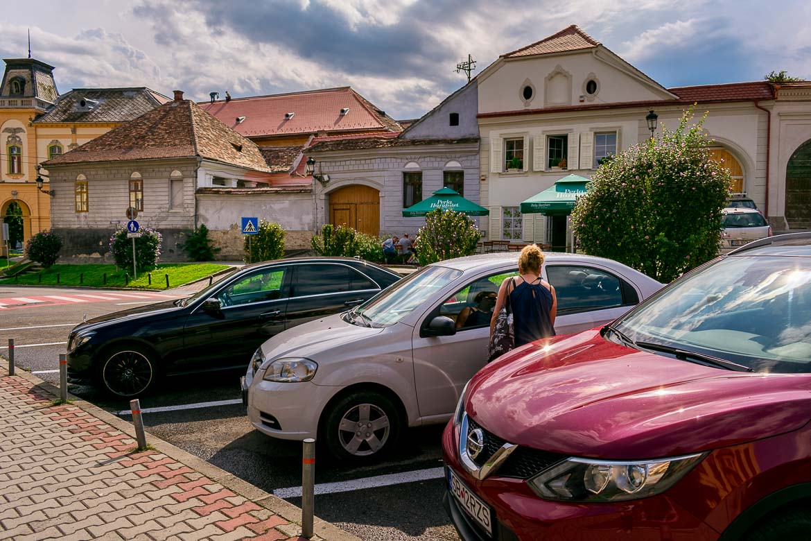 This image shows Maria trying to get in our rental Chevrolet. The white car is parked between two others in Medias Town. There are picturesque colourful houses in the background.