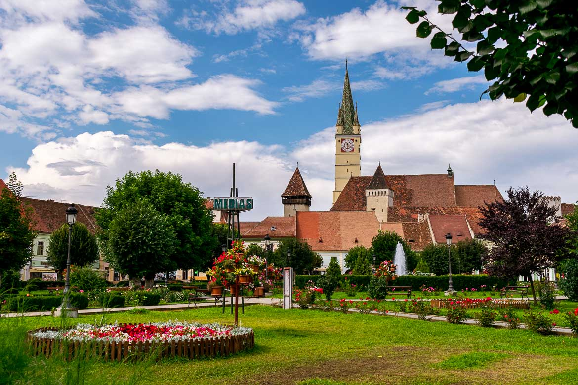 This image shows Piaţa Regele Ferdinand I. This is the main square in Medias Old Town. There is a well cared for garden with a fountain and a sign with the town's name on it. The bell tower of St Margaret's church dominates the sky.