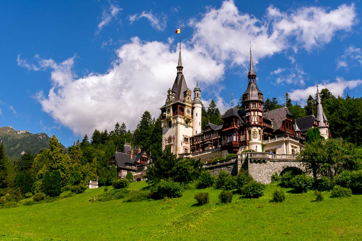 This is an image of Peles Castle. The castle looks magnificent with its elaborate towers and unique architecture. It is surrounded by splendid green landscape.